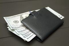 Heap of money and wallet. Dollars money cash on black background. Heap of money and wallet Stock Image