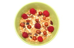 Heap of muesli with hazelnut and raspberries in green bowl Royalty Free Stock Photo