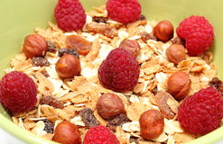 Heap of muesli with hazelnut and raspberries in green bowl Royalty Free Stock Images