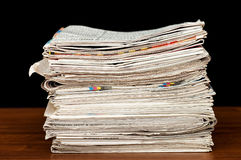 Heap of newspaper on a wooden table stock image