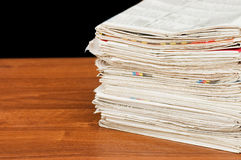 Heap of newspapers on a wooden table Royalty Free Stock Images