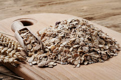 Heap of oat flakes with a scoop on wooden table Stock Image