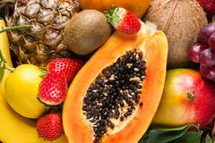Free Heap Of Raw Organic Tropical And Seasonal Summer Fruits Berries Halved Papaya, Coconut Mango Kiwi Bananas Pineapple Strawberries Stock Photos - 139757683