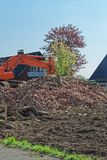 Heap of old bricks and hydraulic bulldozer excavator arm in background stock photos