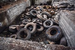 Heap of old car junk tires, used truck rubbish wheels, industrial garbage in abandoned factory Royalty Free Stock Photography