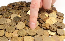 Heap of old coins and finger of woman Stock Images