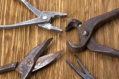 Heap of old instruments on wooden background. Pliers and scissors. Stock Photos