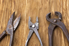 Heap of old instruments on wooden background. Pliers and scissors. Royalty Free Stock Photo