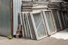 Heap of old wooden window frames with glass outdoors. Broken materials after window energy saving technology upgrade.  royalty free stock images