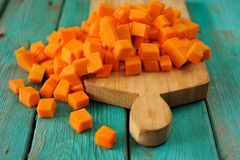 Heap of orange sweet pumpkin cubes on wooden board on turquoise Royalty Free Stock Photos