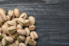 Heap of organic pistachio nuts on wooden table, top view. Space for text royalty free stock images