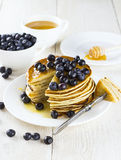 Heap of pancakes the slices of pancakes watered with honey and b. Lueberry, cut off on a fork on a white wooden table Royalty Free Stock Photography