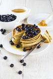 Heap of pancakes the triangular slices of pancakes watered with. Honey and blueberry, cut off on a fork on a white wooden table Royalty Free Stock Images