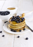Heap of pancakes watered with honey and blueberry on a white woo. Den table Stock Photos
