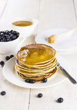 Heap of pancakes watered with honey on a white plate with bilber. Ry on a white wooden table Royalty Free Stock Photography