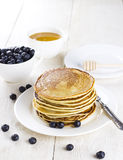 Heap of pancakes on a white plate with blueberry on a white wood. En table Royalty Free Stock Photo