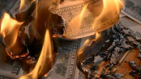 Heap of paper money us dollar flaming on a table. Wreck financial markets concept stock video