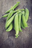 Heap of pea pods on old wood table Stock Images