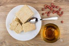 Heap of peanuts, broken peanut halva, tea and teaspoon on table Stock Image