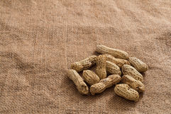 Heap of peanuts on burlap surface background Royalty Free Stock Photos