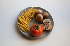 Heap of penne rigate pasta, brown champignons and tomato on plate stock images
