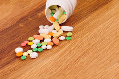 Heap of pills near the opened container on wooden desk Royalty Free Stock Images