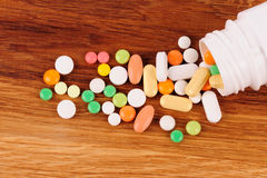 Heap of pills near the opened container on wooden desk Royalty Free Stock Image