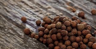 A heap of allspice, on wooden surface. Closeup view. A heap of pimenta placed on wooden surface. Close up view and space for text Stock Photography