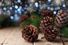 Heap of pine cones and fir tree branch on rustic wooden table. Christmas greeting card. Heap of pine cones and fir tree branch on rustic wooden table. Christmas Stock Photo