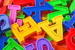 Heap of plastic colored alphabet letters close up Royalty Free Stock Photo