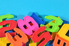 Heap of plastic colored numbers on a blue background Royalty Free Stock Photo