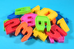 Heap of plastic colored numbers on a blue background Royalty Free Stock Photography