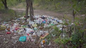 Heap of plastic garbage in forest resort area near path in daytime in summer, moving shot, camera is approaching stock video footage