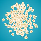 Heap popcorn for movie lies on blue background. Stock Photos