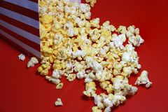 Heap of popcorn from red and white paper box on the red floor. stock images