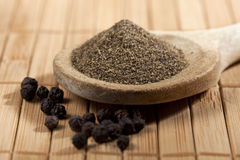 Black Pepper. Heap of powdered black pepper on a wooden spoon and peppercorns, shallow depth of field royalty free stock image