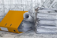 Heap of project drawings in yellow folder. Big heap of design and project drawings in yellow folder on the table surface. White-and-black whatman are background Stock Photography