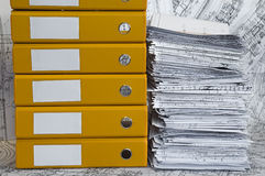 Heap of project drawings in yellow folder. Big heap of design and project drawings in yellow folder on the table surface. Black-and-white whatman are background Stock Photos