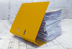 Heap of project drawings in yellow folder. Big heap of design and project drawings in yellow folder on the table surface. White whatman are background Stock Photography