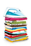 Heap of pure clothes with an iron. Isolated on white Stock Images