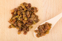 Heap of raisins and wooden spoon on board Royalty Free Stock Photo
