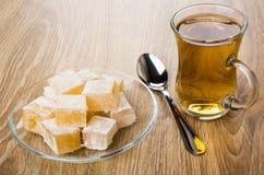 Rakhat-lukum in saucer, cup of tea and teaspoon. Heap of rakhat-lukum in transparent saucer, cup of tea and teaspoon on wooden table Royalty Free Stock Image