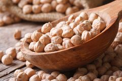 Heap of raw chickpeas in a wooden spoon macro horizontal Stock Image