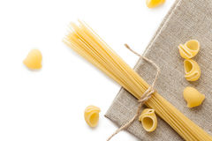 Heap of raw macaroni shells and spaghetti on brown bagging, selec Royalty Free Stock Photo