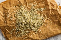 Heap of raw, organic hemp seeds on brown paper from above stock photo