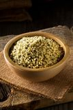 Heap of raw, organic hemp seeds in wooden bowl on burlap on rustic table royalty free stock image