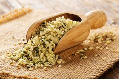 Heap of raw, organic hemp seeds in wooden scoop on burlap on rustic table stock image