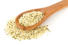Heap of raw, organic hemp seeds on wooden spoon over white royalty free stock photos
