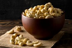 Heap of raw, organic, whole cashew nut kernels in wooden bowl on Stock Images