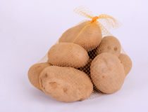 Heap of raw potatoes in yellow string bag. On white background. Close-up stock photography